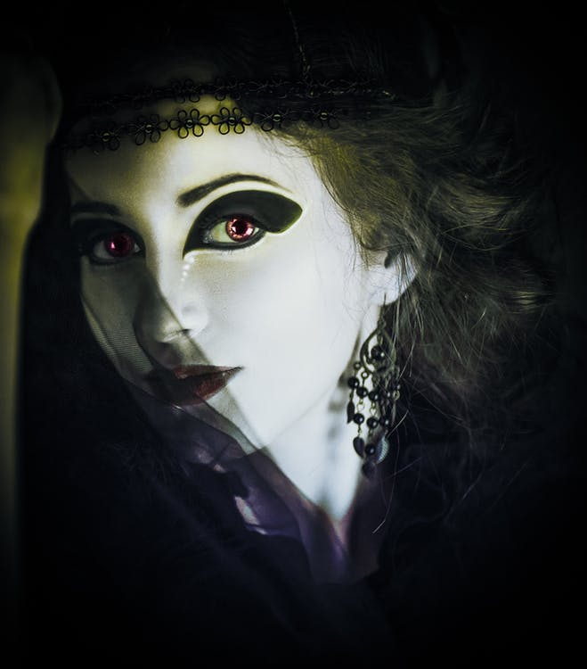 Vampire with red eyes and dark makeup