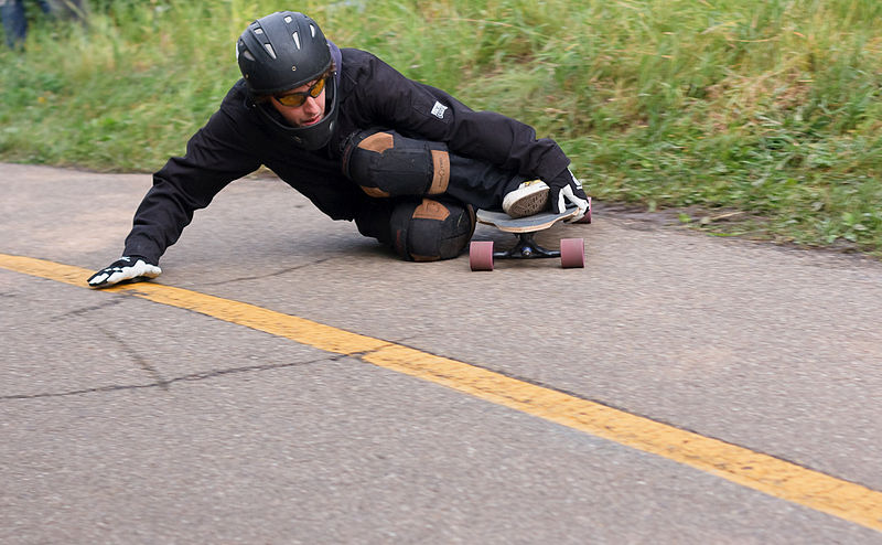 A man performing a trick on a carving longboard.