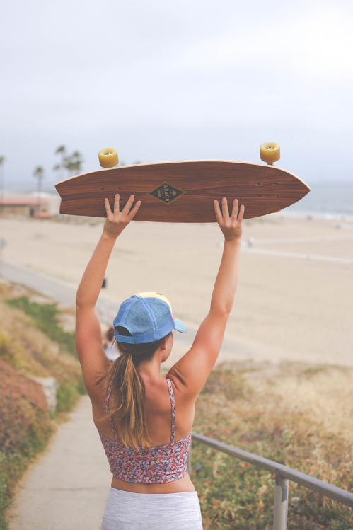 A woman holding her fishtail longboard above her head.A woman holding her fishtail longboard above her head.