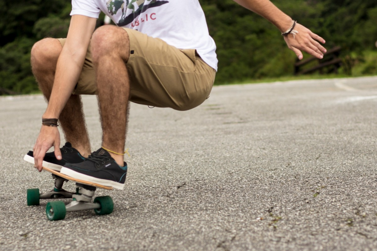 A man performing a trick on a drop down longboard.